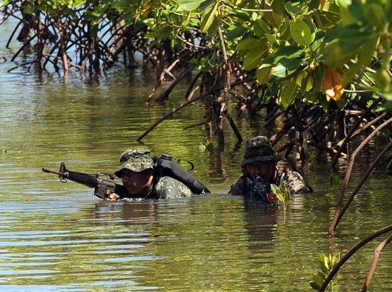 Những người lính Philippines và lính Mỹ lội qua khu rừng ngập nước. Họ luyện tập chiến đấu chống kẻ thù. Ảnh: AFP