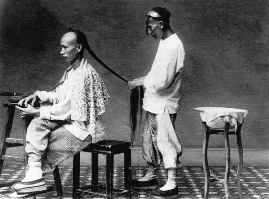 Một đầy tớ thắt bím cho chủ. Theo lệnh của triểu nhà Thanh, tất cả đàn ông Trung Quốc đều phải để bím tóc. Ảnh: GEO EPOCHE