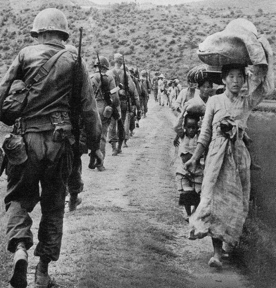 Lính Mỹ trên đường ra mặt trận gặp người dân chạy nạn, tháng 8 năm 1950. Ảnh: GEO EPOCHE
