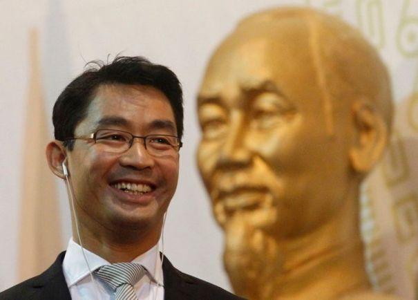 Rösler đứng trước một bức tượng bán thân vàng sáng bóng của nhà lãnh đạo cách mạng Việt Nam  Hồ Chí Minh.