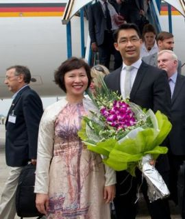 Tại sân bay ở Hà Nội, Rösler được Thứ trưởng Bộ Công Thương Hồ Thị Kim Thoa chào đón với hoa.