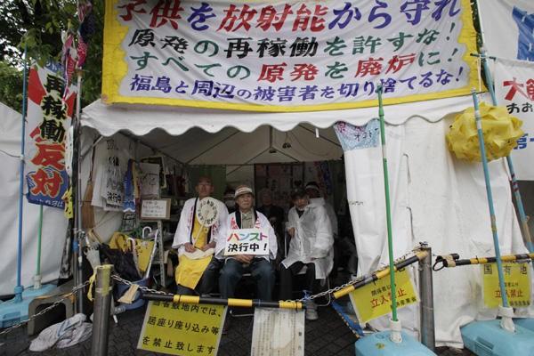 Các nhà hoạt động chống năng lượng nguyên tử Taro Fuchigami (phải), Taichi Masakiyo (giữa) và một tu sĩ Phật giáo đang tuyệt thực trong một căn lều trước Bộ Kinh tế, Thương mại và Công nghiệp Nhật Bản. Hình: Shizuo Kambayashi/AP