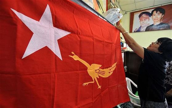 Các thành viên của Liên đoàn Quốc gia vì Dân chủ Myanmar (NLD) phô bày biểu tượng mới của họ trên một lá cờ tại trụ sở NLD ở Yangon. Hình: http://www.telegraph.co.uk