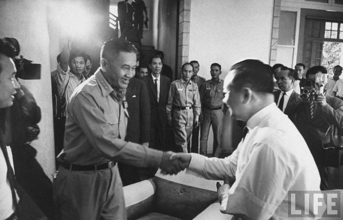 23 tháng Ba 1964, Tướng Minh bắt tay bác sĩ Lê Khắc Quyến, một thành viên trong Thượng Hội Đồng Quốc Gia.