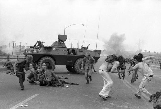Quân lính Nam Việt Nam và nhóm phóng viên truyền hình Phương Tây tìm chỗ trú ẩn trước đạn pháo của người Bắc Việt ở cầu Tân Cảng, Sài Gòn, 28 tháng Tư 1975. Hình: AP Photo/Hoanh