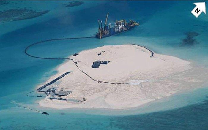 ... vào ngày 25 tháng Hai 2014, bức ảnh này được chụp. Nó cho thấy Trung Quốc đã xây một hòn đảo nhân tạo trên rạn san hô. Bên cạnh nhà giàn cũ (ở phía dưới bên trái) đã có thêm nhiều kết cấu vào thời điểm này, trong số đó rõ ràng là một đường băng. Hai tuần sau đó…. Hình: AFP/ DFA