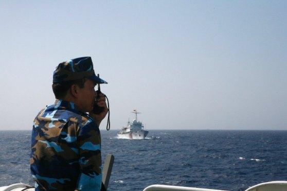 Một người lính hải quân Việt Nam đang quan sát một cihếc tàu của lực lượng hải giám Trung Quốc. Hình: Reuters