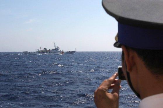 Một thành viên trên tàu Cảnh sát Biển Việt Nam 4033 đang quay phim chiếc tàu hải giám Trung Quốc 3411. Hình: Reuters