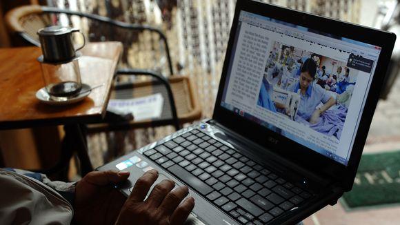 Đọc tin tức trong quán cà phê. Hình: Hoang Dinh Nam/AFP/Getty Images