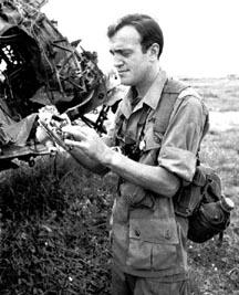 Peter Arnett đứng cạnh một chiếc A 1 Skyraider đã cháy rụi vào ngày 12 tháng Mười 1965 ở gần Biên Hòa