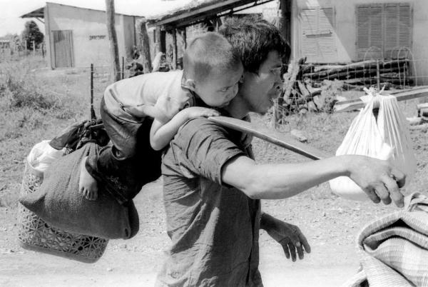 Cha và con trên đường chạy tỵ nạn ở Trảng Bom, 23 tháng Tư 1975.