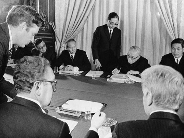 23 Tháng Giêng 1973, Paris, Pháp --- Đại sứ William H. Sullivan (dưới bên phải) và Xuân Thủy (trên bên phải) xem Tiến sĩ Henry Kissinger (ở giữa thấp hơn) và Lê Đức Thọ (thứ hai từ trên bên phải) ký kết Hiệp định Hòa bình Paris. Hình: Bettmann / Corbis