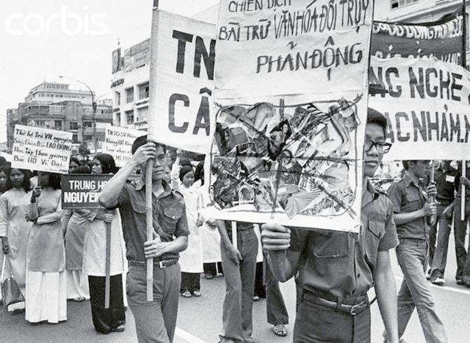 """Sài Gòn, 29 tháng Năm 1975, học sinh sinh viên biểu tình chống """"văn hóa đồi trụy phản động"""" như là một phần của chiến dịch đốt sách ở Nam Việt Nam. Ước tính có hàng chục ngàn quyển sách và băng thu đã bị đốt cháy kể từ khi chiến dịch bắt đầu vao ngày 21 tháng Năm. Tất cả các nhà sách đều bị đóng cửa bởi sắc lệnh cấm bán sách và băng ghi được sản xuất trong thời gian của chế độ cũ."""