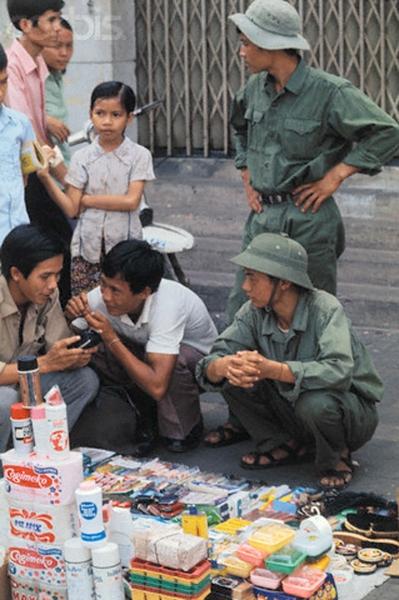 Sài Gòn, 29 tháng Năm: Những người bán hàng chợ đen vẫn kinh doanh như bình thường các món hàng trộm ra từ PX. Nhưng người mua bây giờ là những người lính của Chính phủ Lâm thời.