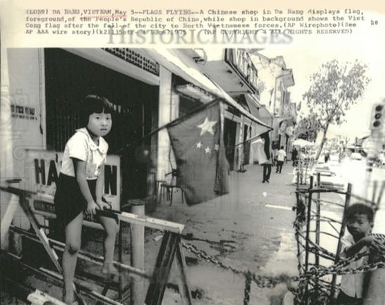 Đà Nẵng, 05 tháng Năm 1975: Một cửa hiệu người Hoa ở Đà Nẵng, ở phía trước, treo cờ nước CHNDTH, trong khi cửa hàng ở phía sau  treo cờ Việt Cộng, sau khi thành phố thất thủ về tay các lực lượng Bắc Việt.
