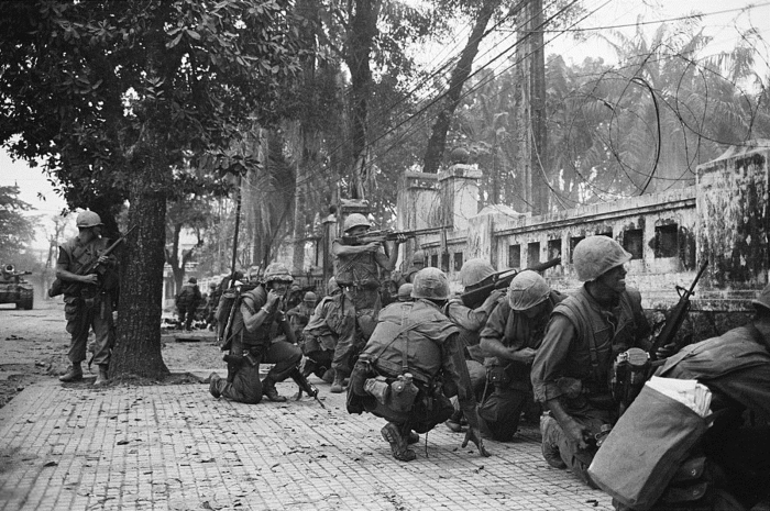 Hue, South Vietnam --- 2/4/1968-Hue, South Viet Nam: U.S. Marines keeping lowbecause of intense sniper fire battle communist units which seized two thirds of the ancient imperial Capital. The Marines were pinned don behind this wall near the old citadel and radiod for support. U.S. spokesmen reported that leathernecks hauled down the North Vietnamese flag after seven days of fighting and recaptured the city. --- Image by © Bettmann/CORBIS