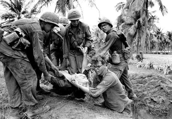 Lính Mỹ với một đồng đội bị thương sau một trận đánh gần Bồng Sơn, Việt Nam, trong tháng Ba 1967. Dana Stone/Associated Press