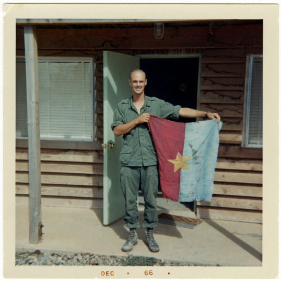 Marsh Carter cầm lá cờ của kẻ địch ở Việt Nam, một tháng trước cuộc tập kích ở Quảng Nam.