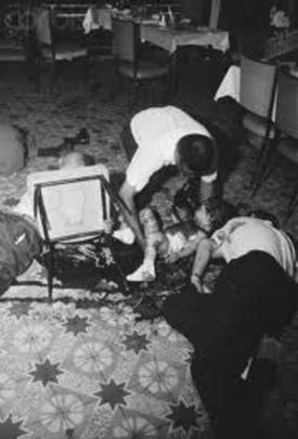 Thiếu Tá Bộ Binh Mỹ Abel Vela đang giúp một em bé bị thương tại nhà hàng Mỹ Cảnh. Xác của ba em và mẹ em nằm kề. Em đã sống sót nhờ ba mẹ em ngồi che khi vụ nỗ bom xảy ra.