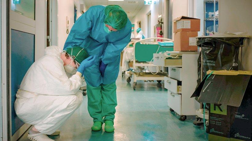 Một cảnh trong một bệnh viện ở Bắc Ý. Người y tá ngồi xuống vì kiệt quệ.